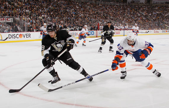 PITTSBURGH, PA - MAY 3:  Kris Letang #58 of the Pittsburgh Penguins moves the puck against Brian Strait #37 of the New York Islanders in Game Two of the Eastern Conference Quarterfinals during the 2013 NHL Stanley Cup Playoffs at Consol Energy Center on May 3, 2013 in Pittsburgh, Pennsylvania.  (Photo by Gregory Shamus/NHLI via Getty Images)