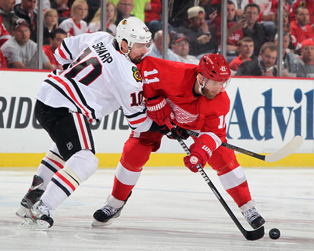 DETROIT, MI - MAY 27:  Patrick Sharp #10 of the Chicago Blackhawks and Daniel Cleary #11 of the Detroit Red Wings battle for the puck during Game Six of the Western Conference Semifinals during the 2013 NHL Stanley Cup Playoffs at Joe Louis Arena on May 27, 2013 in Detroit, Michigan.  (Photo by Dave Reginek/NHLI via Getty Images)