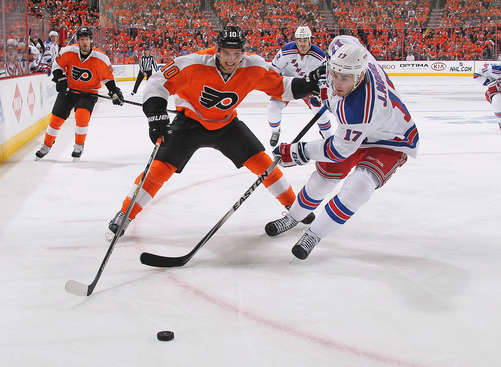 PHILADELPHIA, PA - APRIL 22: Brayden Schenn #10 of the Philadelphia Flyers and John Moore #12 of the New York Rangers battle for the loose puck in Game Three of the First Round of the 2014 Stanley Cup Playoffs at the Wells Fargo Center on April 22, 2014 in Philadelphia, Pennsylvania.  (Photo by Len Redkoles/NHLI via Getty Images)