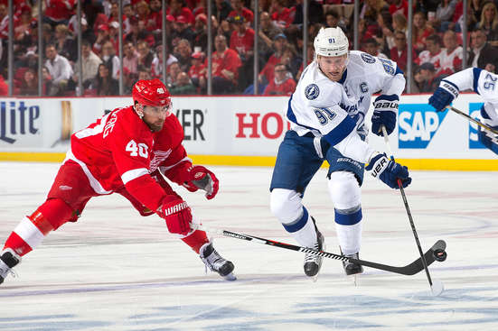 DETROIT, MI - APRIL 23:  Steven Stamkos #91 of the Tampa Bay Lightning skates with the puck as Henrik Zetterberg #40 of the Detroit Red Wings pokes it free in Game Four of the Eastern Conference Quarterfinals during the 2015 NHL Stanley Cup Playoffs on April 23, 2015 at Joe Louis Arena in Detroit, Michigan. (Photo by Dave Reginek/NHLI via Getty Images)