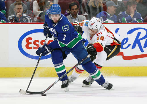 VANCOUVER, BC - APRIL 23:  David Jones #19 of the Calgary Flames pursues Dan Hamhuis #2 of the Vancouver Canucks during Game Five of the Western Conference Quarterfinals during the 2015 NHL Stanley Cup Playoffs at Rogers Arena on April 23, 2015 in Vancouver, British Columbia, Canada.  (Photo by Jeff Vinnick/NHLI via Getty Images)