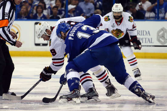 TAMPA, FL - JUNE 03:  Jonathan Toews #19 of the Chicago Blackhawks faces off against Cedric Paquette #13 of the Tampa Bay Lightning to start the first period in Game One of the 2015 NHL Stanley Cup Final at Amalie Arena on June 3, 2015 in Tampa, Florida.  (Photo by Bruce Bennett/Getty Images)