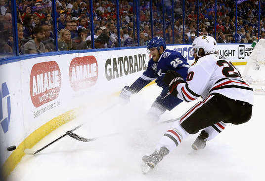 TAMPA, FL - JUNE 13:  Matt Carle #25 of the Tampa Bay Lightning and Brandon Saad #20 of the Chicago Blackhawks chase the puck during the first period of Game Five of the 2015 NHL Stanley Cup Final at Amalie Arena on June 13, 2015 in Tampa, Florida.  (Photo by Dave Sandford/NHLI via Getty Images)