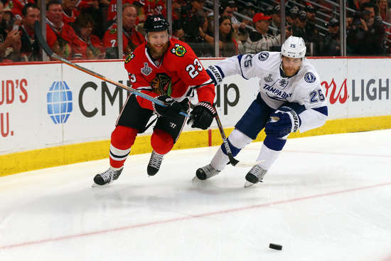 CHICAGO, IL - JUNE 15:  Kris Versteeg #23 of the Chicago Blackhawks fights for the puck against Matt Carle #25 of the Tampa Bay Lightning in the first period of Game Six of the 2015 NHL Stanley Cup Final at the United Center  on June 15, 2015 in Chicago, Illinois.  (Photo by Bruce Bennett/Getty Images)